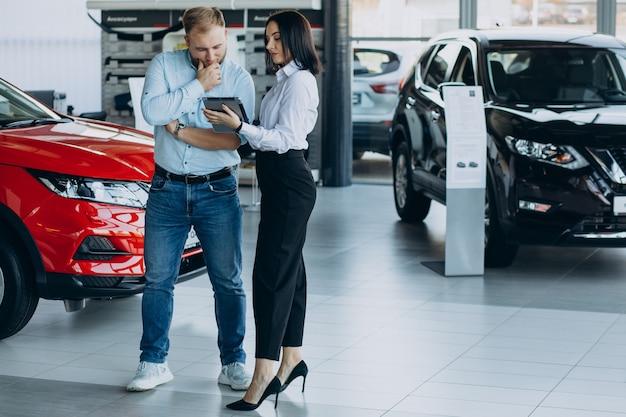 車を選んで販売員と話す男