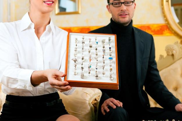 Мужчина выбирает кольцо у ювелира