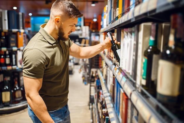 Человек, выбирающий алкогольную продукцию в продуктовом магазине