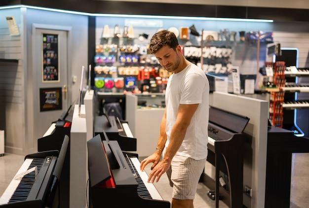 店内で電子ピアノを選ぶ男