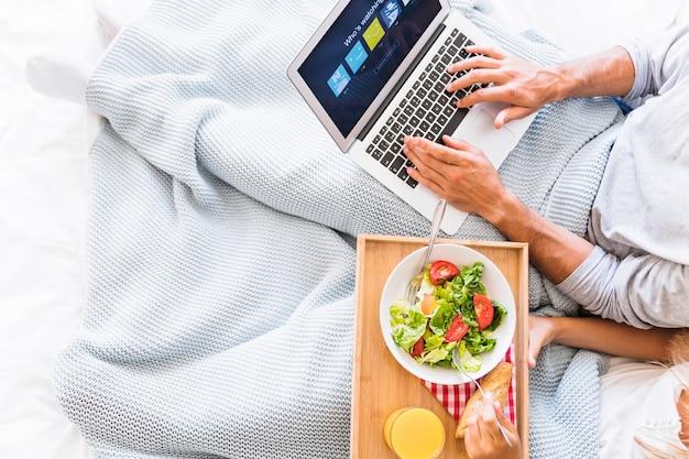 Man choosing netflix account near eating woman
