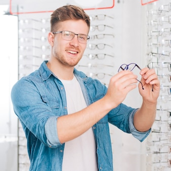 Man choosing new glasses at optometrist