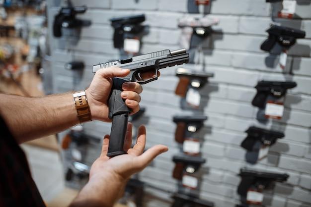 Мужчина выбирает новый пистолет на витрине в оружейном магазине