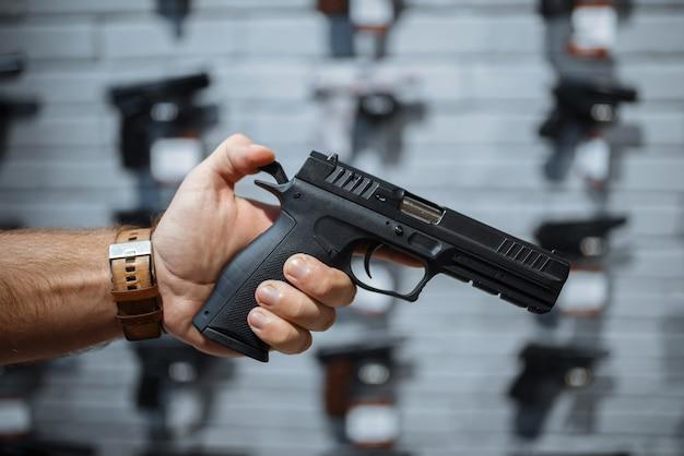 총기 상점에서 쇼케이스에서 새로운 권총을 선택하는 사람