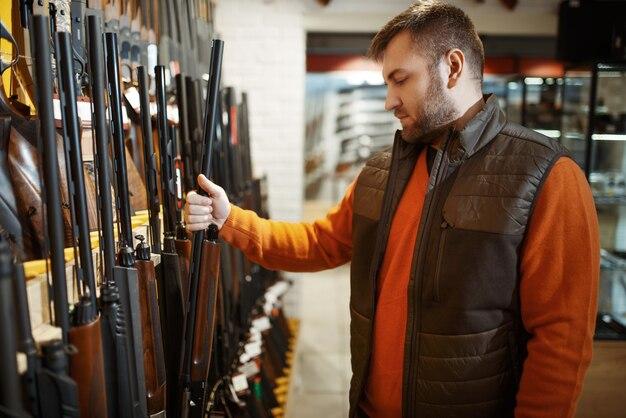 총기 상점에서 쇼케이스에서 소총을 선택하는 사람.