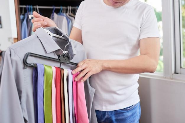 Man choosing tie for shirt
