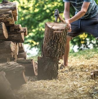 Мужчина рубит дрова топором