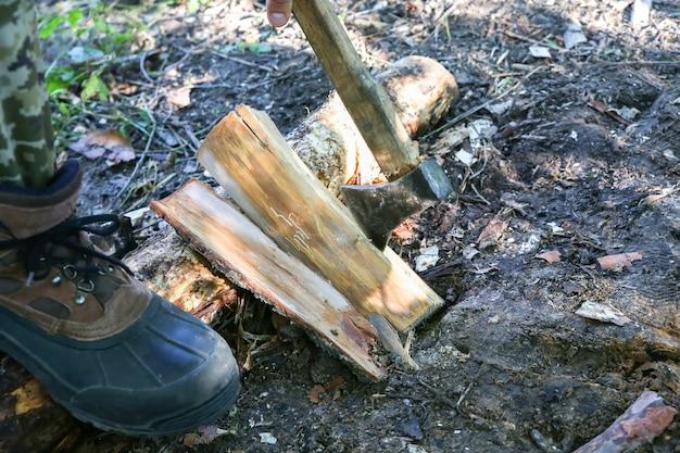 男は屋外で木を切り刻む。斧で森の中の観光客。