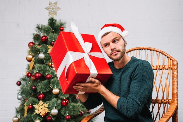 Man in christmas hat holding gift box