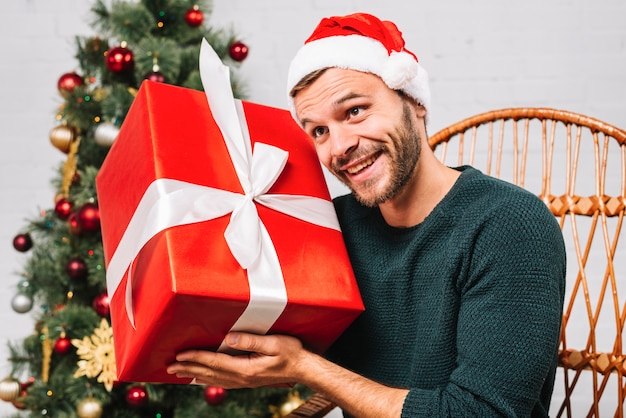 Man in christmas hat holding present box