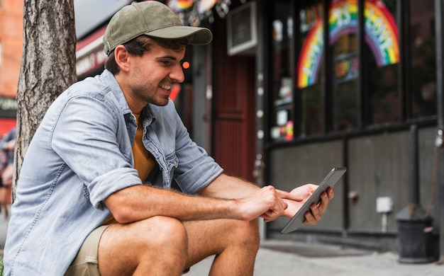 Man in city sitting and using phone