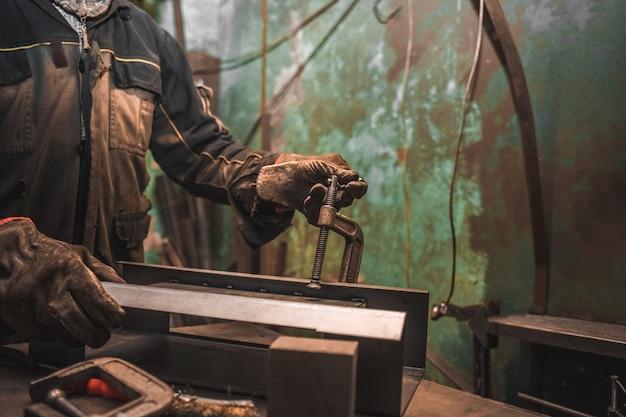 Человек зажимает железные изделия в с-хомуты