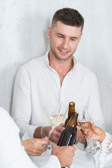 Man clanging bottle of beer with friends