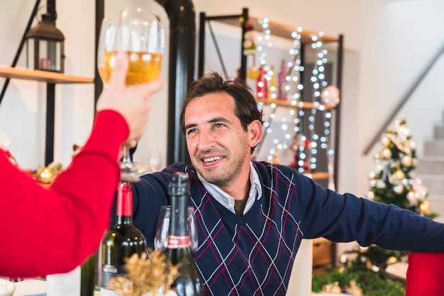 Man clanging glass of wine with wife