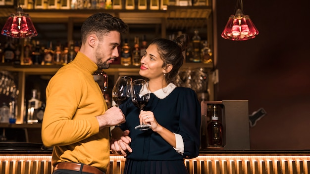Man clanging glasses of wine with smiling woman