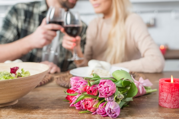 Man clanging glasses with woman at table with flowers and bowl of salad