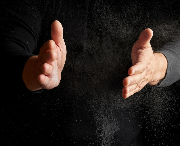 Man claps his hands and scatters to the side a white substance on a black background