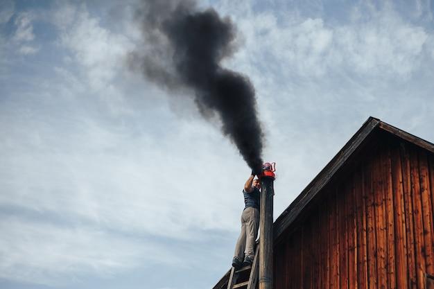 Человек чистит дымоход с помощью вакуума