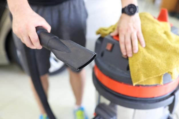 プロの掃除機とマイクロファイバークロスクローズアップカードライからパイプを保持している男性クリーナー