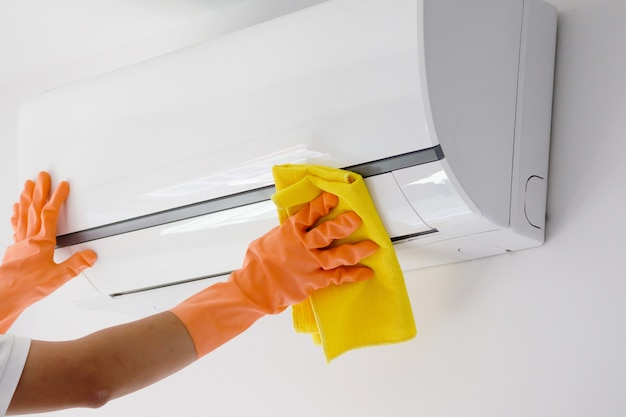 Man cleaning air conditioner with microfiber cloth