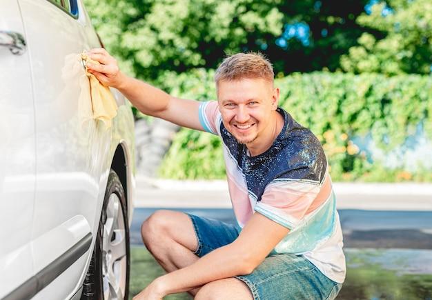 洗車中に雑巾で車のハンドルを洗浄する男