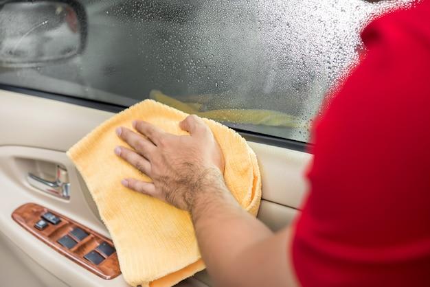 マイクロファイバーの布で車の内部ドアパネルをクリーニング男。