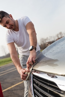 A man cleaning car with microfiber cloth, car detailing (or valeting) concept. selective focus on man's hand.