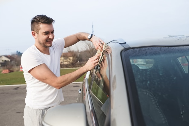 A man cleaning car with microfiber cloth, car detailing (or valeting) concept .