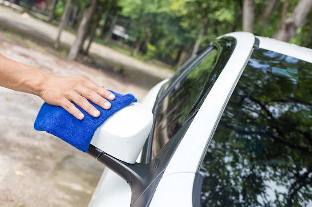 Man cleaning car with microfiber cloth - car detailing and valeting concepts