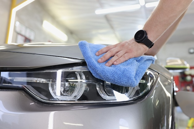 Man cleaning car with microfiber cloth highquality service at car washes concept