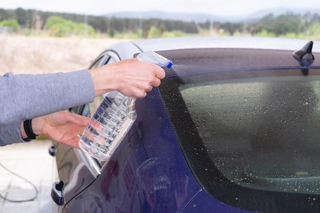 Человек, чистящий машину с распылителем. автомойка.