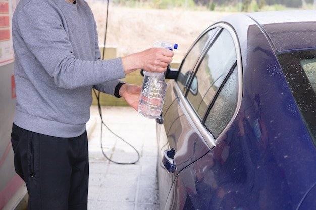 Man cleaning car with spray bottle. car wash.
