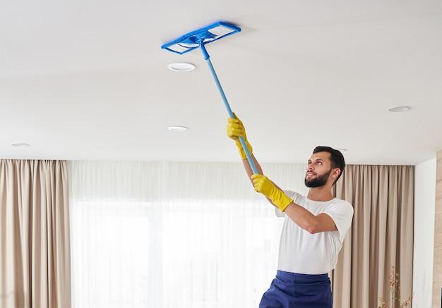 リビングルームの天井とランプを掃除する男。ハウスクリーニングサービスのコンセプト。