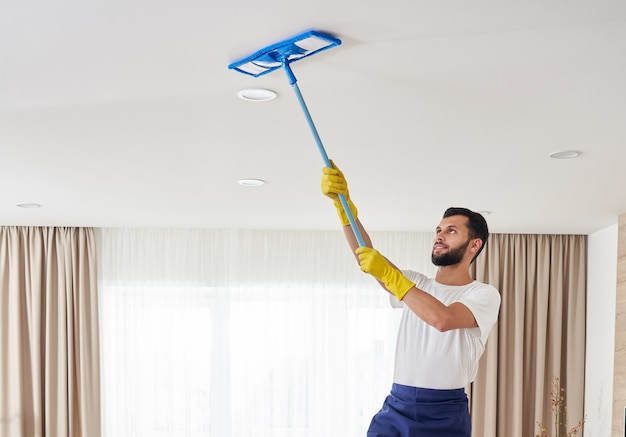 Man cleaning ceiling and lamps in living room. house cleaning service concept.