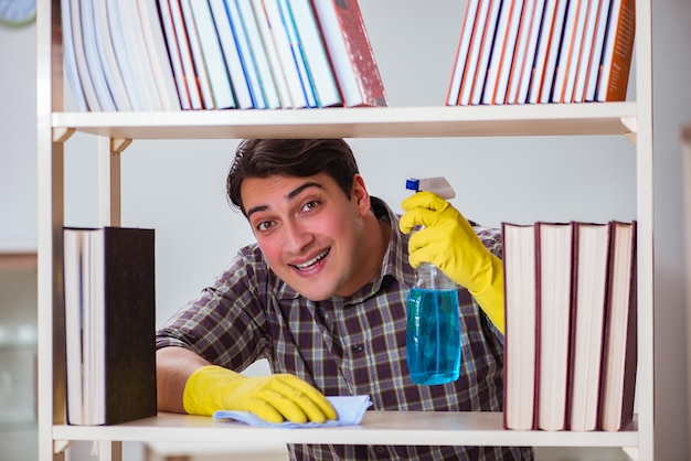 Man cleaning dust from bookshelf