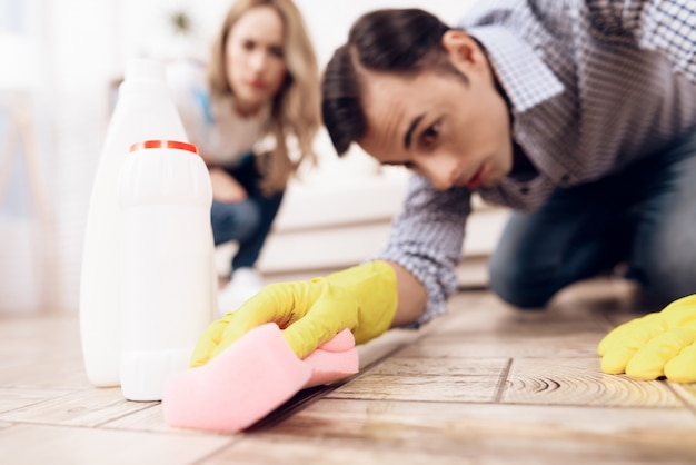 A man cleaning the floor in the apartment of a woman.