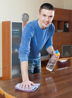 Man cleaning furniture with cleanser and rag at living room