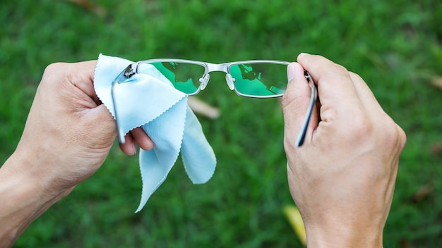 Man cleaning the glasses with microfiber fabric.