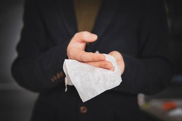 Мужчина чистит руки антибактериальной прокладкой после работы, предотвращая распространение вирусов и бактерий. бизнесмен дезинфицирует руки после рукопожатия