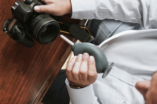 고무 송풍기로 카메라 렌즈를 청소하는 남자