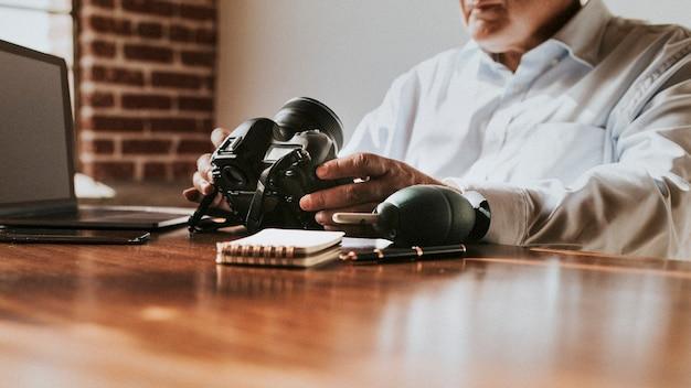ゴム製の送風機でカメラのレンズを掃除している男性