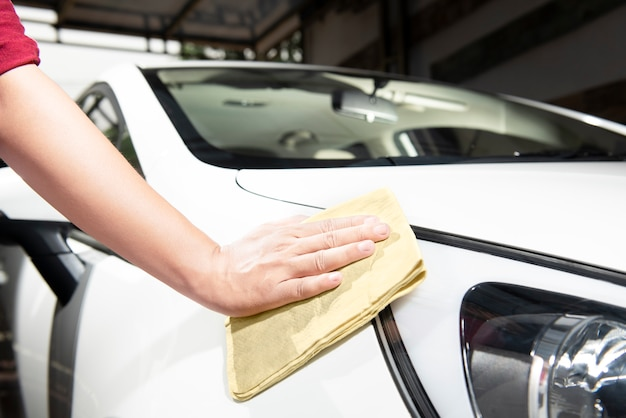 Man cleaning his car with microfiber cloth