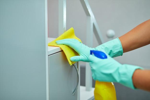 男はタオルと手袋、消毒スプレーボトルで家のテーブルの表面を掃除します。ジェンダーの固定観念を打ち破り、ジェンダーニュートラル。