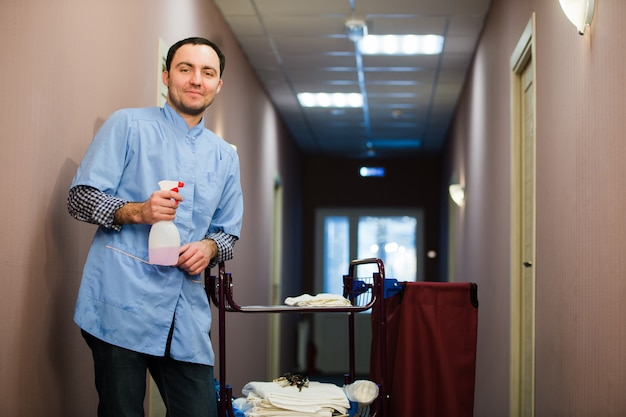 Man cleaning hotel hall wearing blue coat