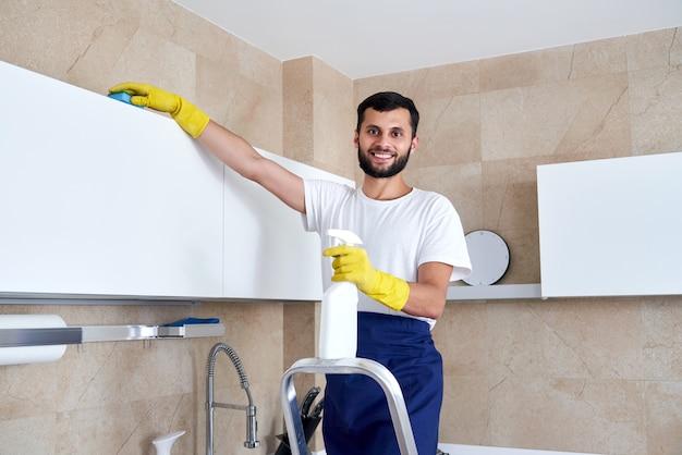 Человек чистка кухонной поверхности высоко стоя на лестнице. концепция клининговых услуг