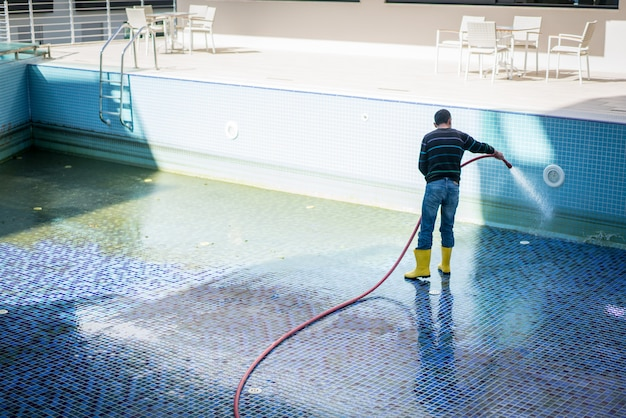 A man cleaning pool