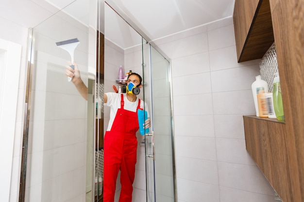 A man cleaning a shower glass