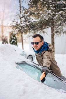 Man cleaning a snow covered car