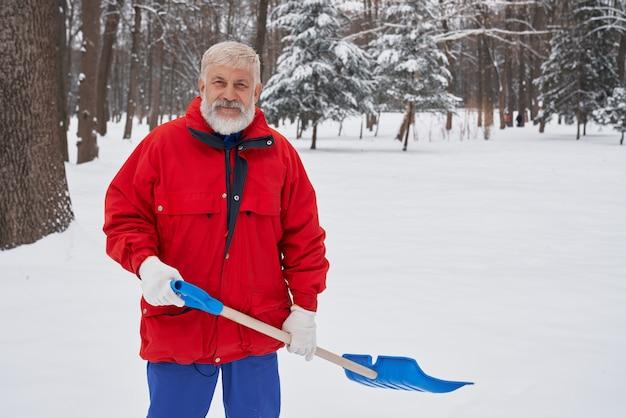 Человек, уборка снега с лопатой в парке.