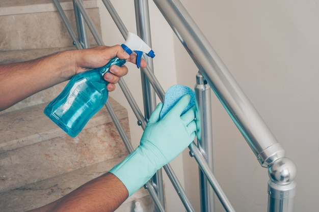 A man cleaning staircase handrail in gloves .
